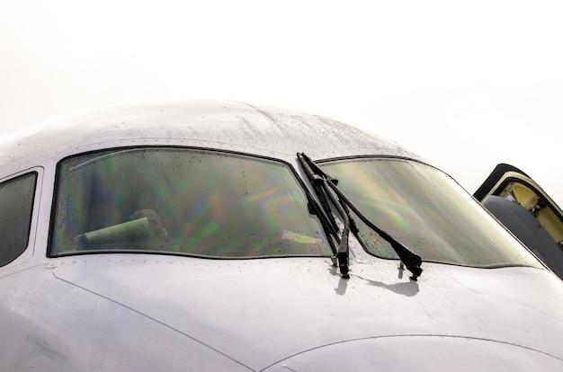 フロントガラスにワイパーが付いたパイロットのコックピット航空機、曇りの日には雨滴。