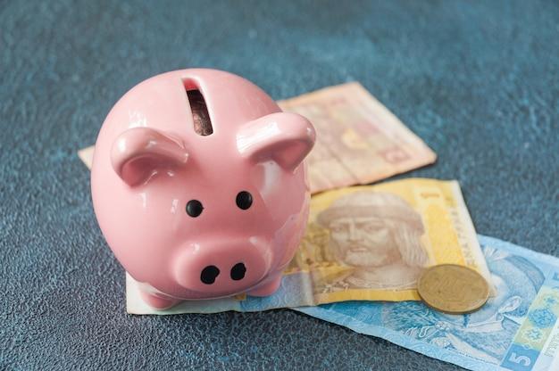 우크라이나 지폐와 동전이 있는 분홍색 돼지 저금통