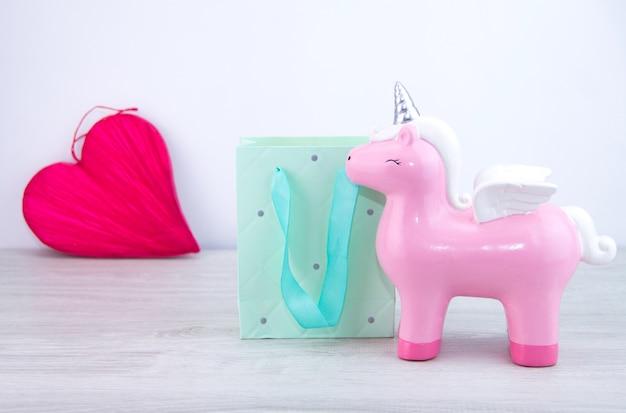 분홍색 유니콘 장난감이 선물 가방 옆에 서 있습니다. 선택적 초점 . 백그라운드에서 붉은 마음. 여자에게 선물.