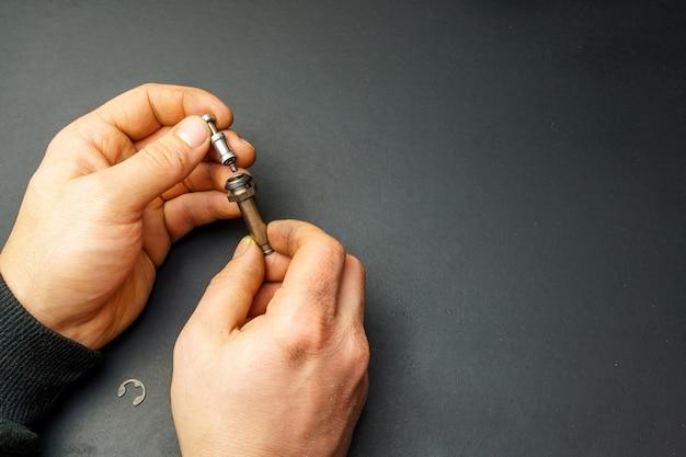 Поршень и цилиндр газовой форсунки газовой рампы автомобиля в мужских грязных руках.
