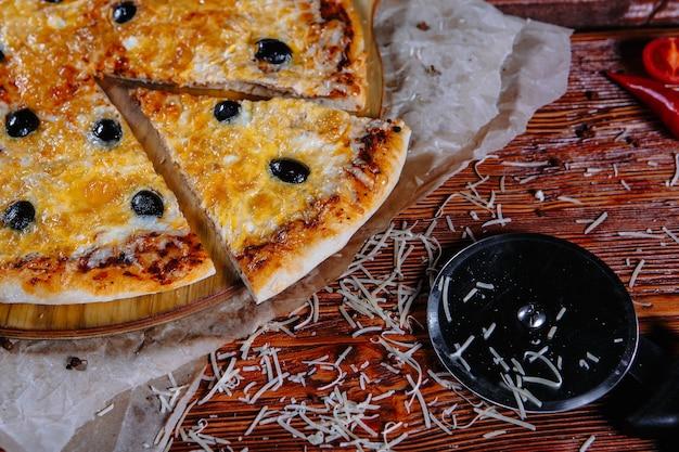 Пицца стоит на кухонном столе, а ингредиенты разбросаны по сторонам.