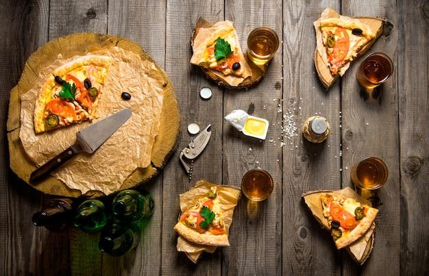ピザパーティー。 4人用のピザとビール。木製のテーブルの上。上面図