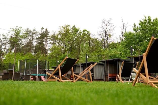 Место для длинных шезлонгов на детской площадке для прыжков на батуте на заднем дворе.