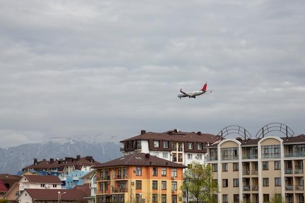비행기가 도시에 도착했습니다. 에어버스는 집 지붕 위로 날아갑니다. 러시아 소치 아들러 지구. 개념: 휴가가 시작되었습니다