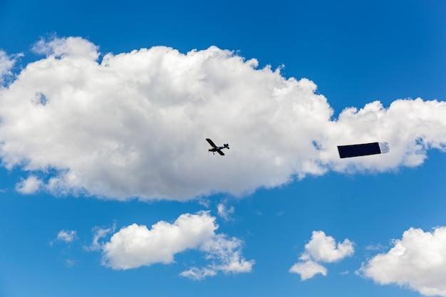 비행기는 광고 표지와 함께 구름 사이에서 하늘을 날고, 하늘에 광고