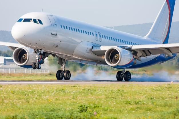 飛行機が着陸します。煙で滑走路に触れる