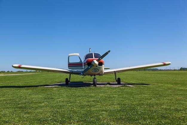 비행기 파이퍼 체로키(piper cherokee)는 화창한 날 푸른 잔디 위에 서 있다 작은 개인 비행장