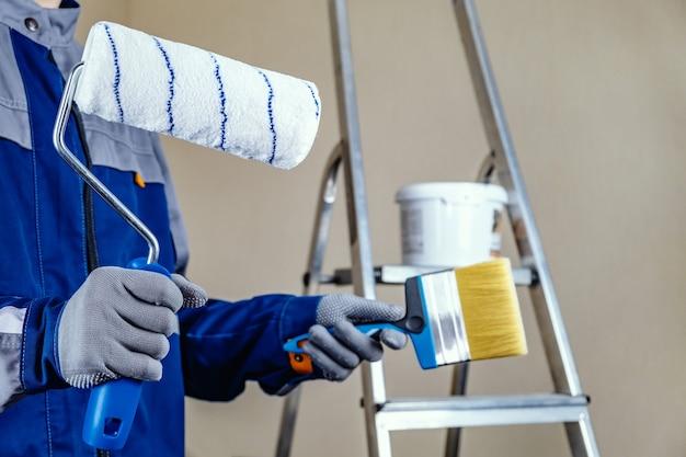 しっくいの画家は壁を塗る準備ができています。ローラーとブラシの手で。背景に脚立とペンキのバケツ。