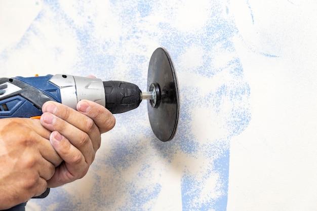 미장이는 샌더로 벽의 표면을 평평하게 만듭니다. 마스터는 표면에서 오래된 페인트를 제거합니다.