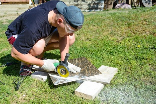 Мастер-штукатур обрезает мраморную плитку вокруг керамического диска.