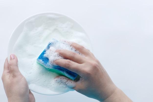 手に泡のプレート、皿洗い