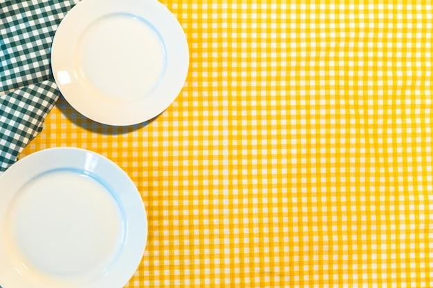 黄色の市松模様のテーブルクロスの上の皿