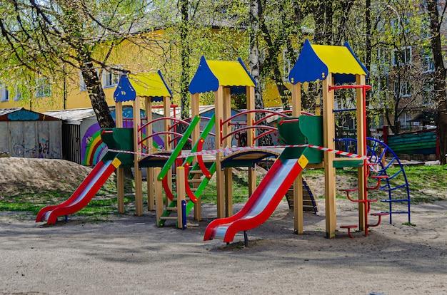 遊び場は禁止されたテープで囲まれています。コロノウイルスのパンデミック(流行)による検疫のため、屋外ゲームの閉鎖された場所