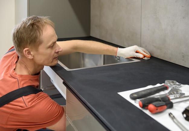 배관공이 부엌 싱크대에 있는 쓰레기 파쇄기의 시작 버튼을 설정하고 있습니다.