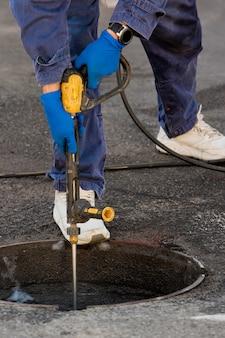 配管工は下水道の問題を解決する準備をしています。トラブルシューティングの修理作業。閉じる。
