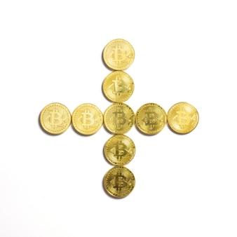Символ плюса выложен из биткойн-монет и изолирован на белом фоне