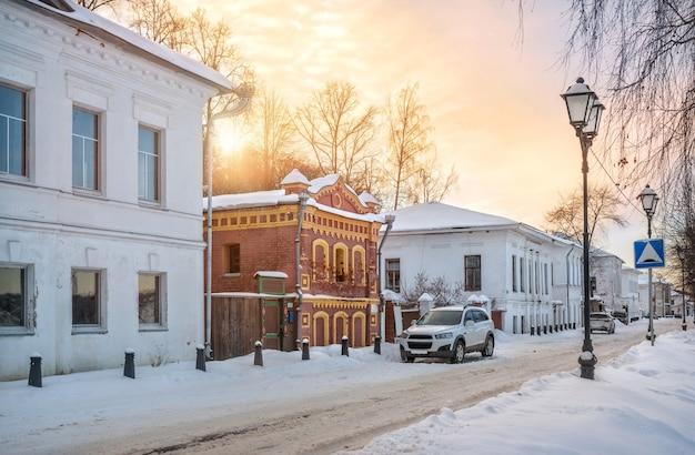 Дом подгорновых на набережной волги в плёсе в снегу в свете заходящего зимнего солнца