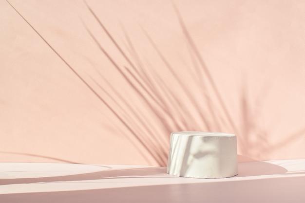 연단은 베이지색이며 콘크리트로 만들어진 기하학적 모양과 자연스러운 그림자가 있습니다. 시멘트로 만든 쇼케이스가 있는 장면. 최소한의 배경입니다. 화장품 프레젠테이션.
