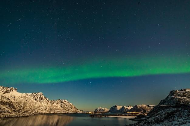 ノルウェーの旅行写真家の山々でオーロラの空の星を狩る極地の北極圏のオーロラ