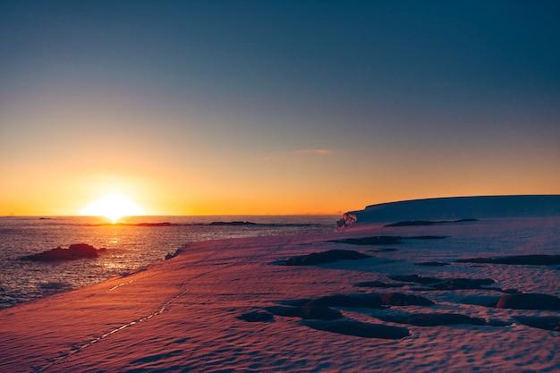 Vernadsky research base로의 극단적인 탐험 중 촬영된 극지방 일몰 일출. 멋진 눈 풍경은 얼음으로 뒤덮인 남극 표면과 태평양입니다.