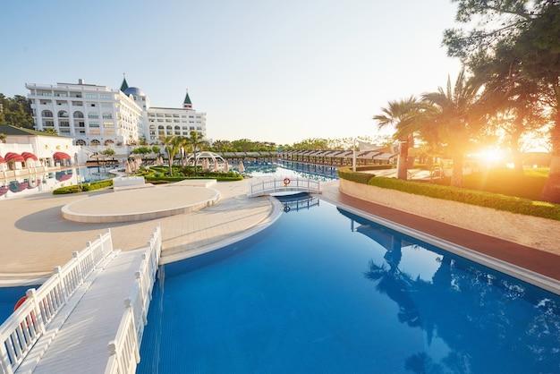 人気のリゾート、アマラドルチェヴィータラグジュアリーホテル。トルコの海岸沿いのプールとウォーターパーク、レクリエーションエリアが夕日にあります。ケメロボ・ケメル。