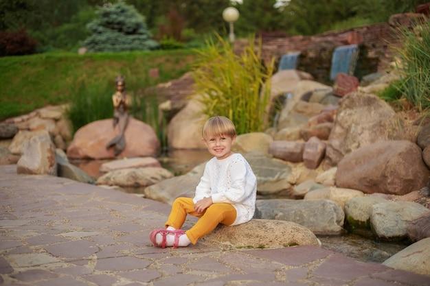 Портрет маленькой девочки с короткими волосами, сидящей на камне в парке