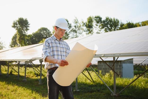 Портрет молодого инженера проверяет фотоэлектрические солнечные батареи