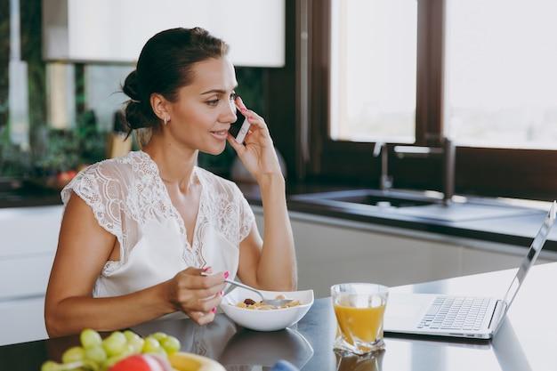 Портрет красивой счастливой женщины разговаривает по мобильному телефону во время завтрака с ноутбуком на столе