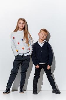 세련 된 청바지 옷을 입고 귀여운 작은 소년과 소녀의 초상화 포즈
