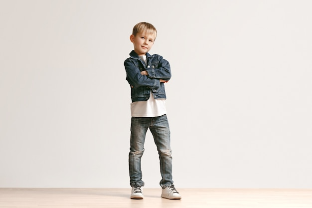 흰색 스튜디오 벽에 카메라를보고 세련 된 청바지 옷에 귀여운 꼬마 소년의 초상화. 키즈 패션 컨셉
