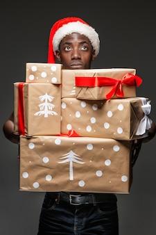 어두운 배경에 선물을 들고 산타 모자를 쓴 잘생긴 젊은 흑인 아프리카 남자의 초상화. 긍정적인 인간의 감정과 메리 크리스마스 개념