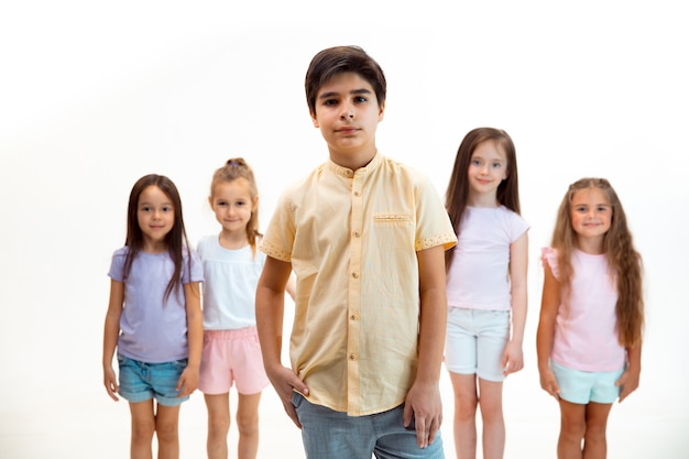 Портрет счастливых милых маленьких детей, мальчика и девочек в стильной повседневной одежде, смотрящих в камеру на фоне белой стены