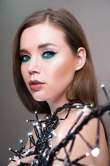 Портрет модели с длинными волосами и идеальной кожей на серой поверхности.