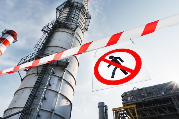 ポスター発電所のパイプの背景に対して通路を囲う赤と白のリボンへの不法侵入は許可されていません。