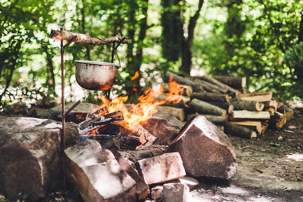 Ночью возле палатки в лесу горит котелок. красивый костер в туристическом лагере в дикой природе.