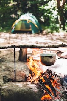 ポットは夜、森のテントの近くで燃えています。野生のツーリストキャンプで美しいキャンプファイヤー。
