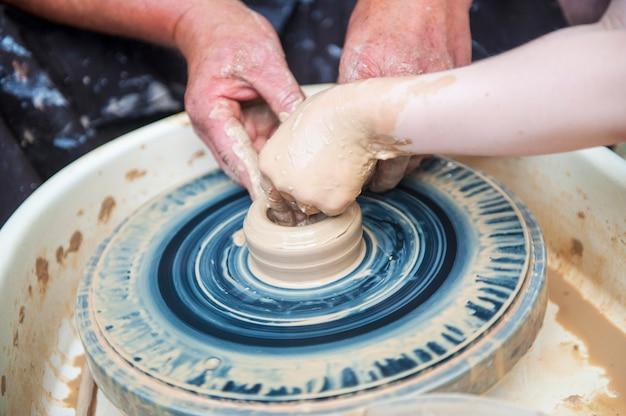 陶芸家はろくろで陶器料理を作ります。ワークショップの彫刻家は、粘土製品をクローズアップします。陶芸家の手。