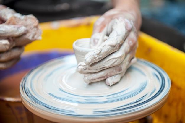 Гончар лепит посуду на гончарном круге. скульптор в мастерской делает крупный план изделия из глины. руки гончара.