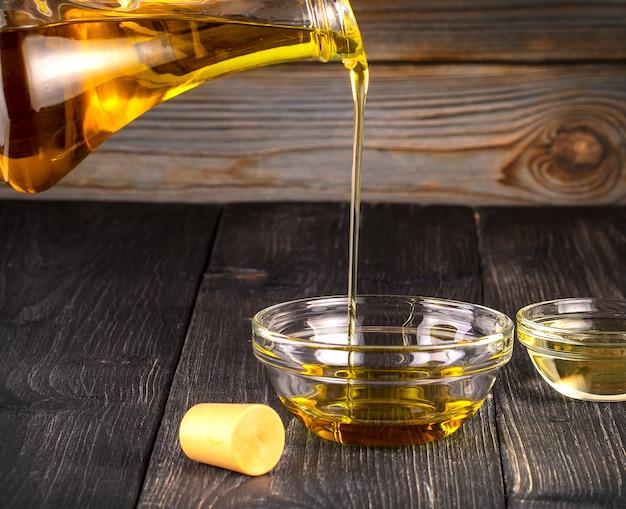 古い木製のテーブルに小さなガラスのコップに食用油を注ぐ