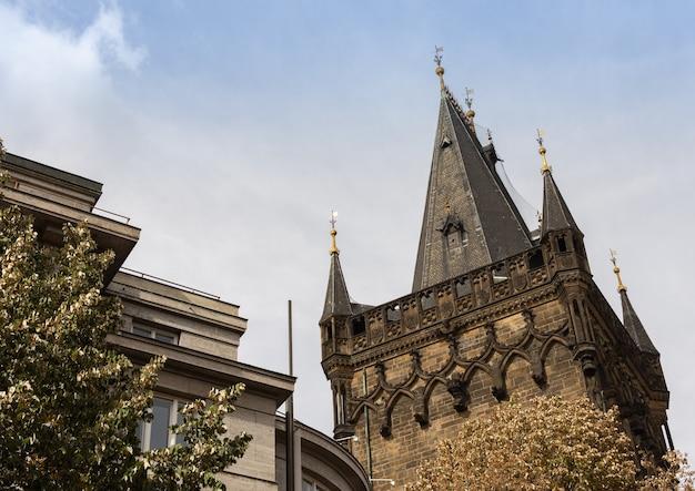 プラハの歴史的中心部にある近代的および古い建物の近くのパウダータワーまたはパウダーゲート
