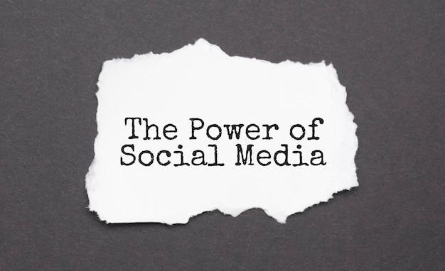 黒い表面に破れた紙に書かれた「the power of social media」のサイン