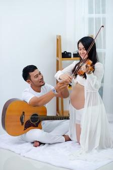 妊娠中の男性と夫は家で楽しく音楽を演奏しています。