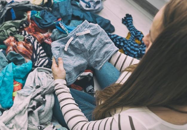 Беременная разбирает детскую одежду