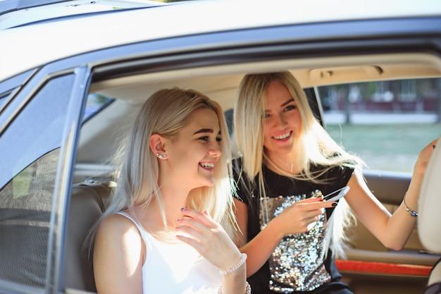 차에 예쁜 유럽 십대 소녀들이 웃고있다.