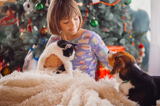 Симпатичная девушка, укрывающая кошку и собаку