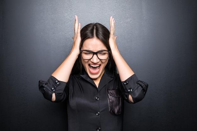 黒い壁に叫び、罵倒する眼鏡をかけたかなり若い怒っている茶色の髪の女性。感情の概念。