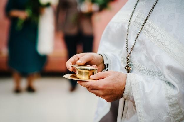 Священник благословляет и подает в чашу кровь божью, вино жениху и невесте. молодожены, пара счастлива на свадебной церемонии в церкви.