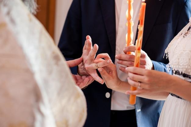 Священник одевает кольца молодоженам.