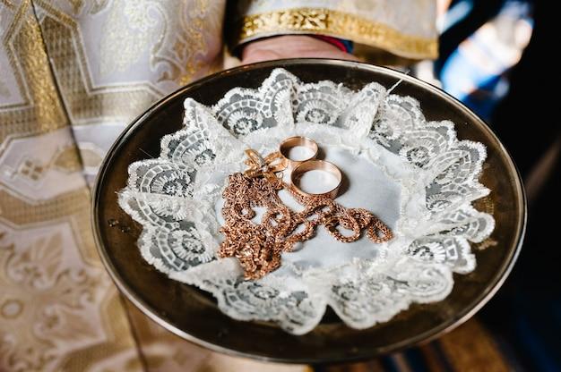 Священник держит на подносе два обручальных кольца и крест для свадебной церемонии.