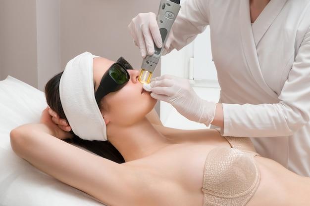 Процедура удаления волос на теле женщины в косметологической клинике лазерная эпиляция